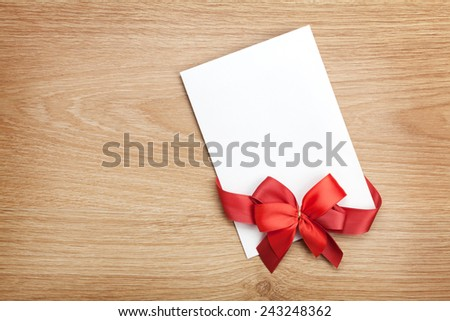 Blank valentines greeting card and red ribbon on wooden background with copy space