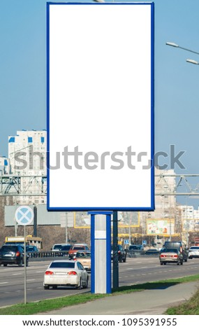 Blank vertical billboard near a highway.