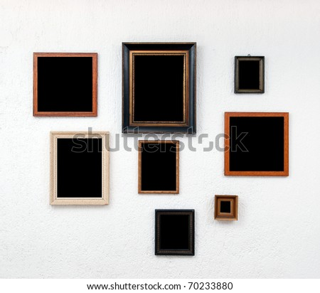 Blank vintage frames on textured white wall