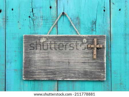 Blank weathered sign with wooden cross hanging by rope on antique teal blue wood door