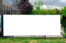 Blank white advertising banner mounted on the fence against office building.