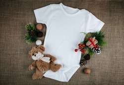Blank white baby Christmas bodysuit mockup. Infant one piece styled bodysuit flat top view on a rustic background.  Copy space. Baby announcement concept.  Mockup-Digital File with Christmas decor.