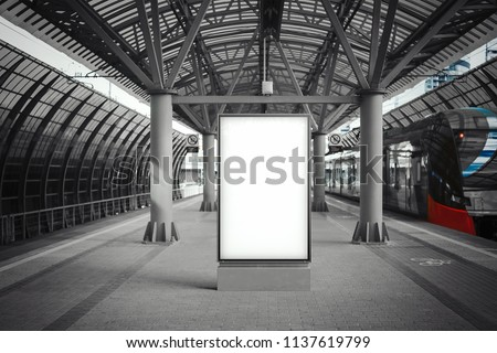 Blank white banner at metro station with arrived train on a background. Train is out of focus and blurred, banner is on focus. Station is monochrome and train is coloured. 3d rendering