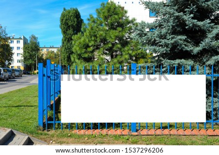 Blank white banner for advertisement on the fence. Residential area on a sunny summer day. ストックフォト ©