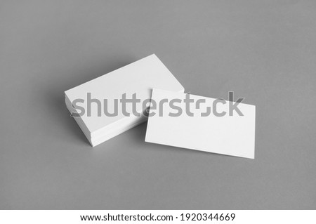 Blank white business cards on gray paper background. Mockup for branding identity. Template for graphic designers portfolios.