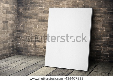 Blank white canvas frame leaning at grunge brick wall and wood floor, Mock up template for adding your design. #436407535