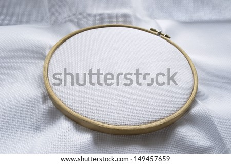 Blank white canvas stretched on the wooden hoop