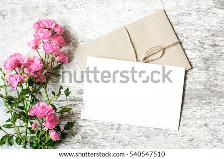 Blank white greeting card and envelope with pink rose flowers mockup on white rustic wood background for creative work design. top view