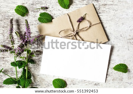 Blank white greeting card and envelope with purple wildflowers of mint mock up on white rustic wood background for creative work design. top view