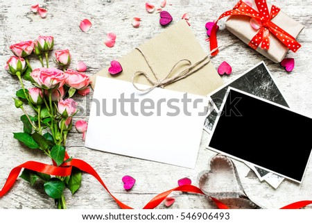 blank white greeting greeting card and blank photo frame with envelope, pink roses, wooden hearts, red ribbon and gift box. valentines day background. top view