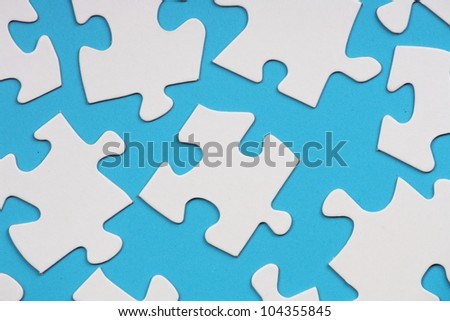 Blank white jigsaw pieces arranged on a blue paper background as a concept for problems and solutions or finding the missing piece as part of a business strategy