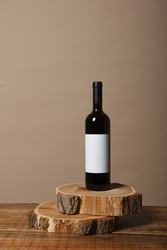 Blank white label mock up on black bottle of unlabeled red wine on a wooden table. Alcohol bottle mockup presentation ready for logo design. Full drink bottle template with empty sticker.