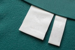 Blank white laundry care clothes label on green fabric texture background