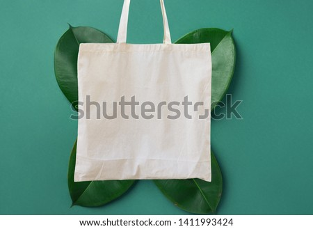Blank white mockup linen cotton tote bag on green leaves foliage background. Zero waste reusable nature friendly materials. Environmental conservation recycling plastic free concept #1411993424