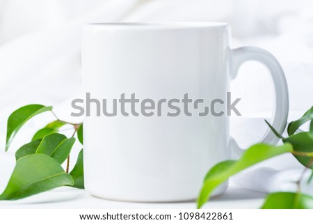 Blank White Mug Mockup on Cotton Linen Fabric Background. Fresh Tree Branches with Green Leaves. Template Space for Creative Artwork Lettering Text Product Promotion Branding. Elegant Feminine Style #1098422861