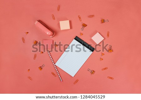 Photo of Blank white note pad paper, pencil, stapler, thumb tacks, paper clips, and adhesive paper over coral color background with free space for text. Image shot from top view.