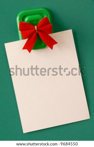 Blank white note paper hanging from magnetic pinup on green background..