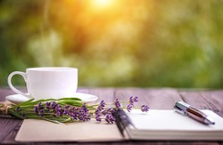 blank white notebook, flowers and cup of coffee on the desk outdoors in the summer