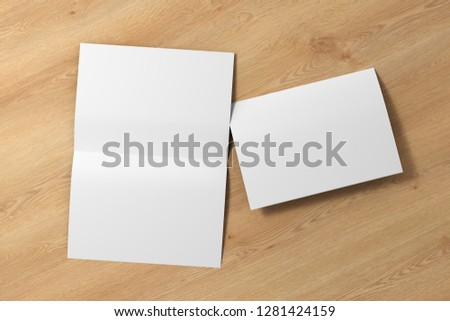 Blank white open and folded half-folded flyer leaflet on wooden background. With clipping path around brochure. 3d illustration