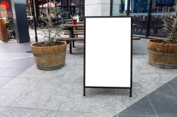 Blank white outdoor advertising stand/sandwich board mock up template. Clear street signage board placed by an outdoor dinning area of a restaurant. Background texture of standee on street.