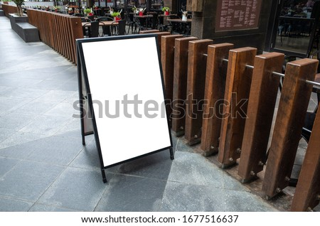 Blank white outdoor advertising stand/sandwich board mock up template. Clear street signage board placed by an outdoor dinning area of a restaurant. Background texture of standee on street. Foto stock ©