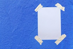 Blank white paper attached to the blue wall with tape.