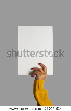 Blank white paper in hand of woman wearing mustard yellow sweater with fingernails painted on grey isolated background for number, letter, words written. (close up, space for text)