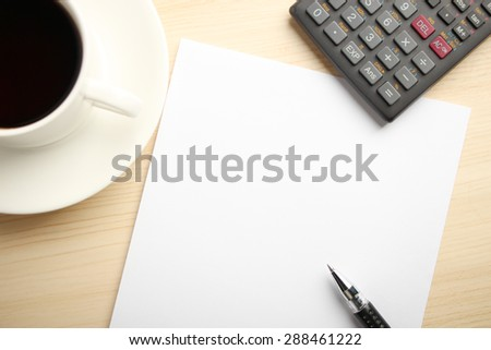 Blank white paper is on the table with calculator and coffee aside.