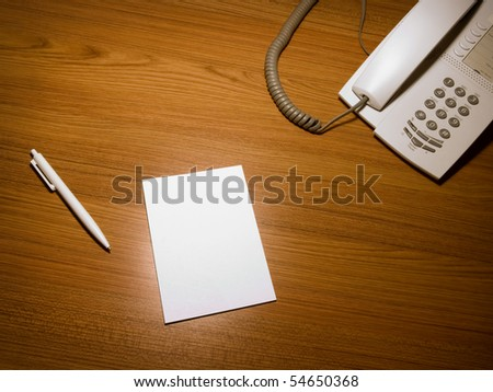Blank white paper on the wooden working desk with the pen and telephone,shot taken from above
