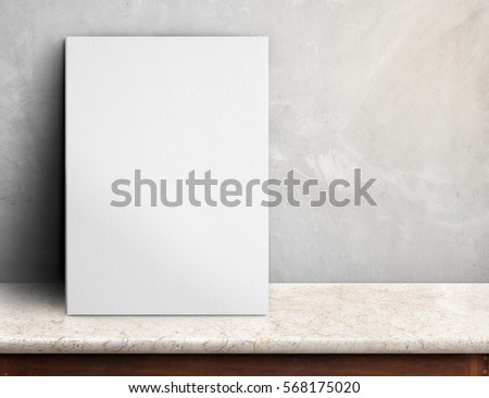 Blank White paper poster on black marble table at grey concrete wall,Template mock up for adding your design and leave space beside frame for adding more text #568175020