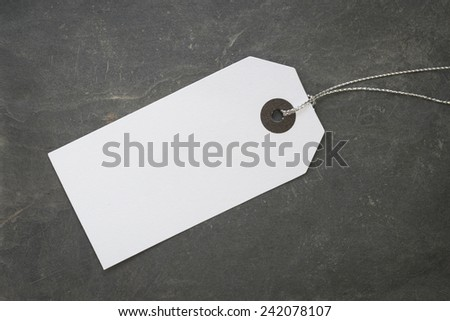 Blank white paper tag on stone surface