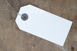 Blank white paper tag on wood surface