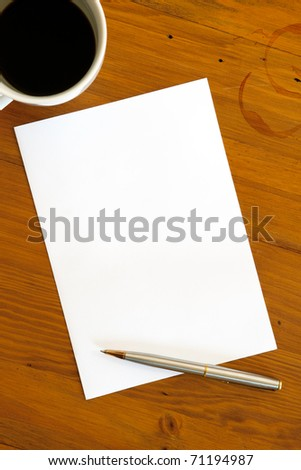 Blank white paper with pen and a half-empty cup of coffee, over coffee-stained timber desk.  Ready for your message.