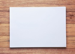 Blank white paper with space on wooden table- vintage filter.