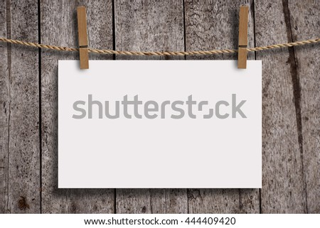 Blank white paper with wood clip on wood wall panels, grunge wood background. Blank paper for your text, copyspace or your design.