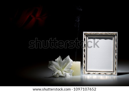 Blank white picture frame, with smoky candle and white lily flower on dark background with red decoration