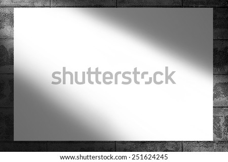 Blank white poster hanging on brick wall black and white background-light sunrays through the wall