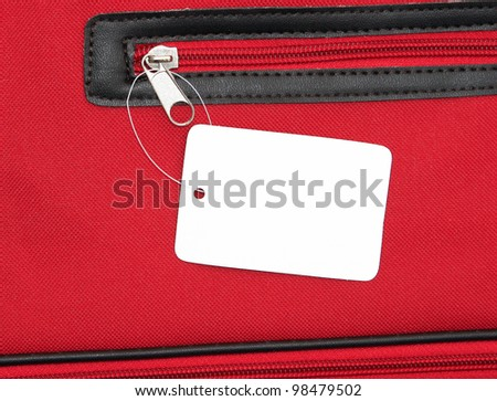 Blank white price tag on red zippered bag for your text