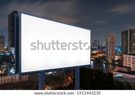 Blank white road billboard with Bangkok cityscape background at night time. Street advertising poster, mock up, 3D rendering. Side view. The concept of marketing communication to sell idea.