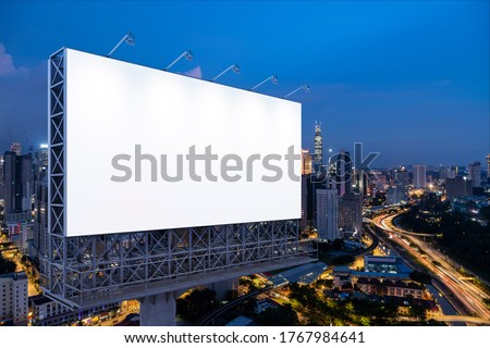 Blank white road billboard with KL cityscape background at night time. Street advertising poster, mock up, 3D rendering. Side view. The concept of marketing communication to promote or sell idea. Stock foto ©