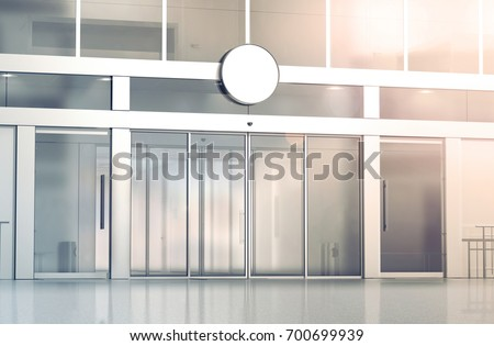 Blank white round signage mockup on the store glass sliding doors entrance, 3d rendering. Commercial building automatic entry, banner mock up. Closed transparent business centre facade, front view.