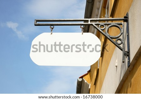 Blank, white  shop sign hanging in a wrought iron bracket on yellow wall against a blue sky