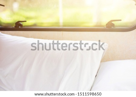 Blank White soft Pillows on comfortable bed near window with sunlight in the morning. rest, interior, comfort and bedding concept.