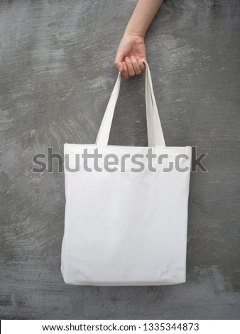 Blank white tote bag canvas fabric with handle mock up design. Close up of woman hand holding eco or reusable shopping bag on grunge grey wall. No plastic bag and ecology concept. Vertical.