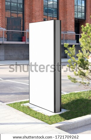 Blank white vertical pylon stand mockup brick building, side view. Empty information stand on street for advertise mock up. Clear vertical monitor or totem for affiche or ad mokcup template. Foto stock ©