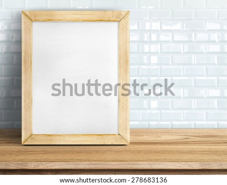 Blank whiteboard wood frame on wooden table at white tile wall,Template mock up for adding your design and leave space beside frame for adding more text.