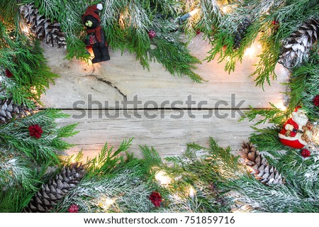 blank wood sign with christmas tree garland border with snow holiday lights pine cones