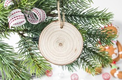Blank wood slice disk ornament on christmas tree with decor, round holiday ornament mockup