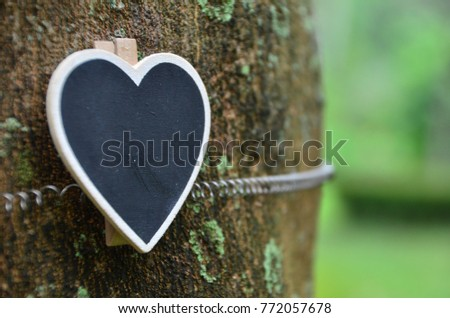 Blank wooden board place on timber tree with the element of loving nature. Purposely for text insertion. Selective focus. #772057678
