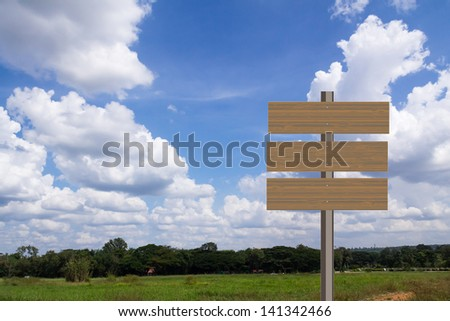 Blank wooden sign in green grass field over blue sky background - stock photo